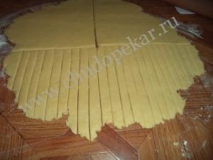Раскатать тесто в пласт и нарезать полосками.