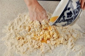 Замешиваем яйца в муку.